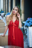 Beautiful blonde lady in red dress on White Square Stock Image