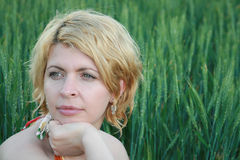 Beautiful blonde lady in wheat field at sunset Stock Photo