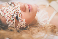 Beautiful blonde lady with white lace mask over Stock Photo