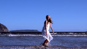 Beautiful blonde leaping up in white dress on sunny day at the beach stock video footage