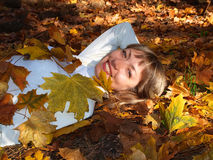 Beautiful blonde with leaves in the autumn forest Stock Photos