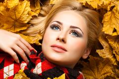 The beautiful blonde lies in autumn foliage Stock Photos