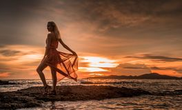 A beautiful blonde in a light red dress is standing by the sea on a background of bright sunset stock image