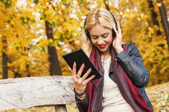 Beautiful blonde listens to the music through a digital tablet Stock Photos