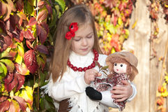 Beautiful blonde little girl with doll stock photo