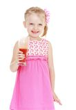 Beautiful blonde little girl holding a glass of Stock Images