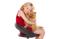 Beautiful blonde little girl holding  her dog wearing red dress Royalty Free Stock Photo