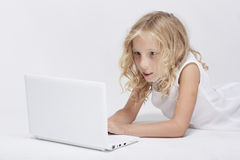 Beautiful blonde little girl with netbook, white background Royalty Free Stock Photo