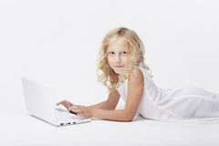 Beautiful blonde little girl with netbook, white background Royalty Free Stock Photos