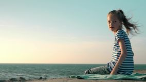 Beautiful blonde little girl in a striped t-shirt sits on the beach windy day copyspace concept health vacation. Beautiful blonde little girl in a striped t stock video footage
