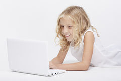 Beautiful blonde little girl in white, computer Stock Photo