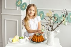 Beautiful blonde little girl in a white shirt is sitting at the holiday table near a vase with sprigs decorated with royalty free stock image