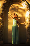 Beautiful blonde with a long curly hair in a long evening dress in static outdoors near retro vintage building in summer sunset Stock Images