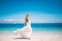 Beautiful blonde long hair bride in long white dress running on the white sand beach. Tropical turquois sea on the background. stock photos