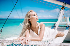 Beautiful blonde long hair bride on wedding day ready for travel by sail boat. Happy island lifestyle. White sand, blue cloudy sky royalty free stock images