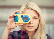 Beautiful blonde with long hair looking at the camera and holding in hands toy camera. Close up. Royalty Free Stock Photo