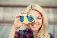 Beautiful blonde with long hair looking at the camera, smiling and holding in hands toy camera. Close up. Stock Images
