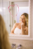 Beautiful blonde looking a big heart on mirror. In the bathroom at home royalty free stock image