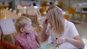 Beautiful blonde loving mother with son and daughter eating in cozy cafe on weekends. stock footage