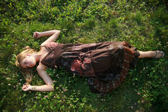 Beautiful blonde lying on the grass. Young woman lying on the grass Royalty Free Stock Image