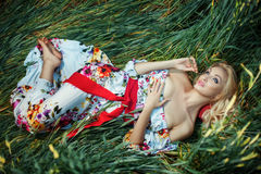 Beautiful blonde lying on the grass crumpled. Stock Photo