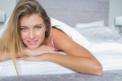Beautiful blonde lying in her bed smiling Stock Photography