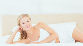 Beautiful blonde lying on her bed smiling at camera Stock Photography