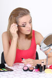 Beautiful blonde with make up accessories and mirror Stock Photo