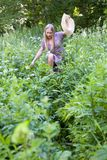 A beautiful blonde makes her way through thickets of tall grass. royalty free stock photography