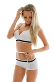 Beautiful blonde is measuring her waist Royalty Free Stock Image