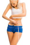 Beautiful blonde is measuring her waist Royalty Free Stock Photos