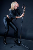 Beautiful blonde with a microphone Stock Images