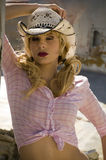 Beautiful blonde model. In a pink blouse and a cowboy hat Stock Image