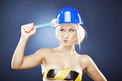Beautiful blonde model with adjustable wrench. Royalty Free Stock Image