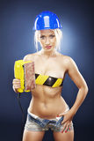 Beautiful blonde model with an electric sander. Stock Photos