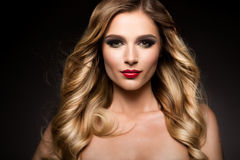 Beautiful blonde model girl with long curly hair . Hairstyle wavy curls . Red lips. royalty free stock photos