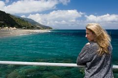 Blonde woman outdoor, azure blue sea background, beach and mountan Royalty Free Stock Image