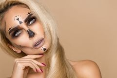 Beautiful blonde woman in Halloween makeup and beautiful hair on a beige background in the studio. Skeleton, monster and witch. royalty free stock photography