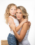 Beautiful blonde mother and daughter hug each other stock photo