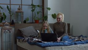 Cheerful family having video chat using laptop. Beautiful blonde mother and her lovely daughter using laptop pc anfd having video chat with grandmother while stock video footage