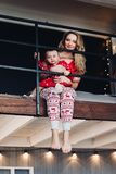 Beautiful mother with little daughter in Christmas pajamas reading book at kitchen. stock photos