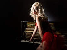 Free Beautiful Blonde Musician In Red Corset Standing Near The Piano. Vintage Style Beautiful Woman. Stock Photography - 95341092