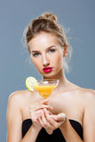 Beautiful blonde naked girl holding cocktail over grey background. Young beautiful blonde naked girl holding cocktail over grey background. Copy space Stock Image