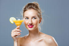 Beautiful blonde naked girl smiling, holding cocktail over grey background. Young beautiful blonde naked girl smiling, holding cocktail over grey background Stock Photography