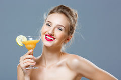 Beautiful blonde naked girl smiling, holding cocktail over grey background. Stock Photography
