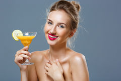 Beautiful blonde naked girl smiling, holding cocktail over grey background. Royalty Free Stock Photos