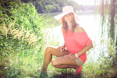 Beautiful  blonde in a nature. Beautiful blonde on a pink shirt and shorts and hat kneels in a nature, at a pond, fashion photography Royalty Free Stock Photos