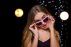 Beautiful blonde in a nightclub at the disco. Girl peeking out from under sunglasses Royalty Free Stock Photography