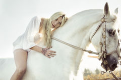 Beautiful blonde nymph with her horse Stock Photo