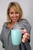 Beautiful Blonde Offers a Cup of Coffee Royalty Free Stock Image